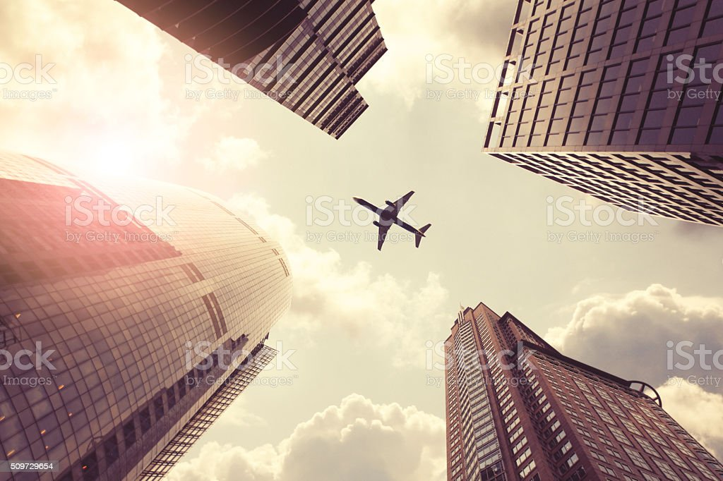 Airplane flying above skyscrapers stock photo