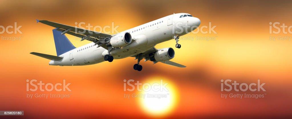 Airplane flying at sunrise stock photo