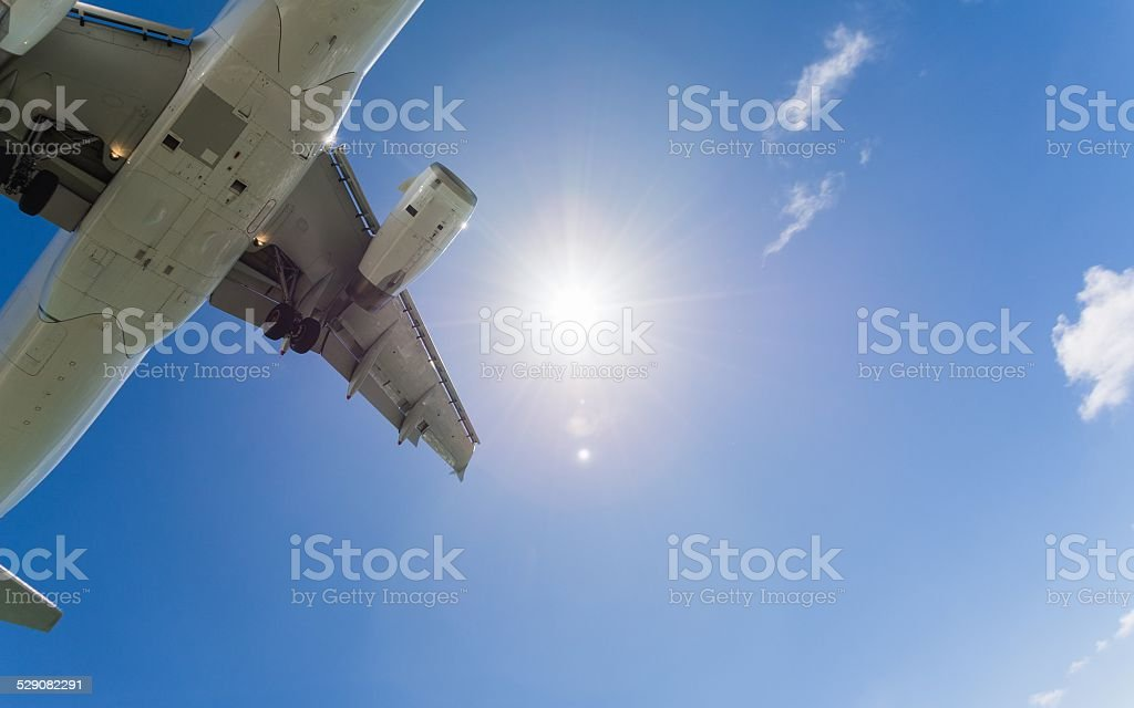 Airplane flying close to ground while landing stock photo