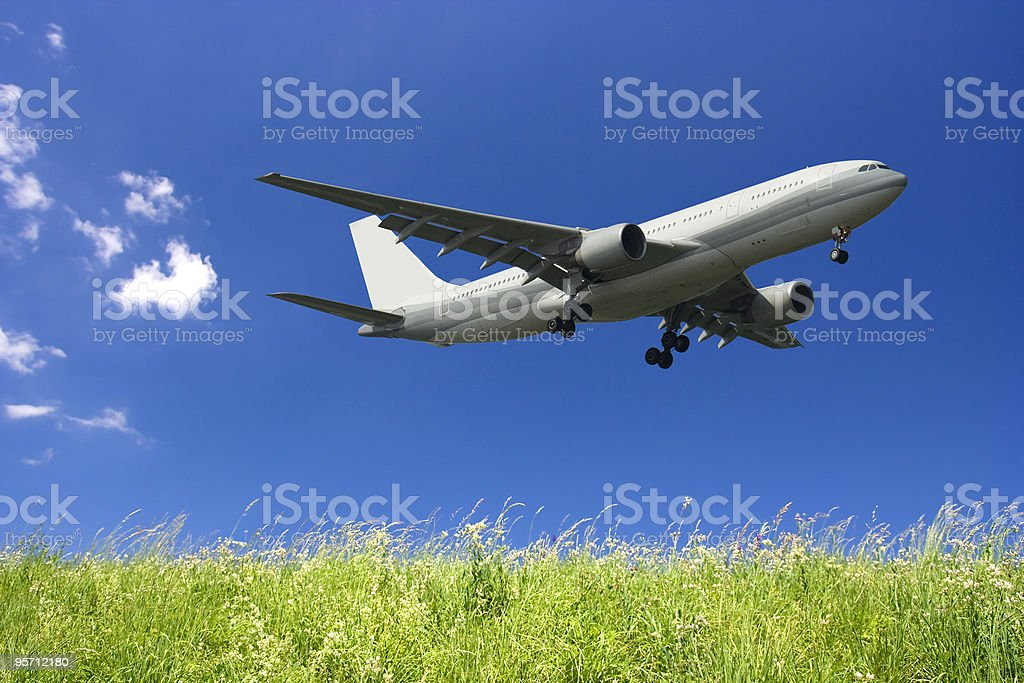Airplane Flying in a Blue Sky and Green Grass royalty-free stock photo