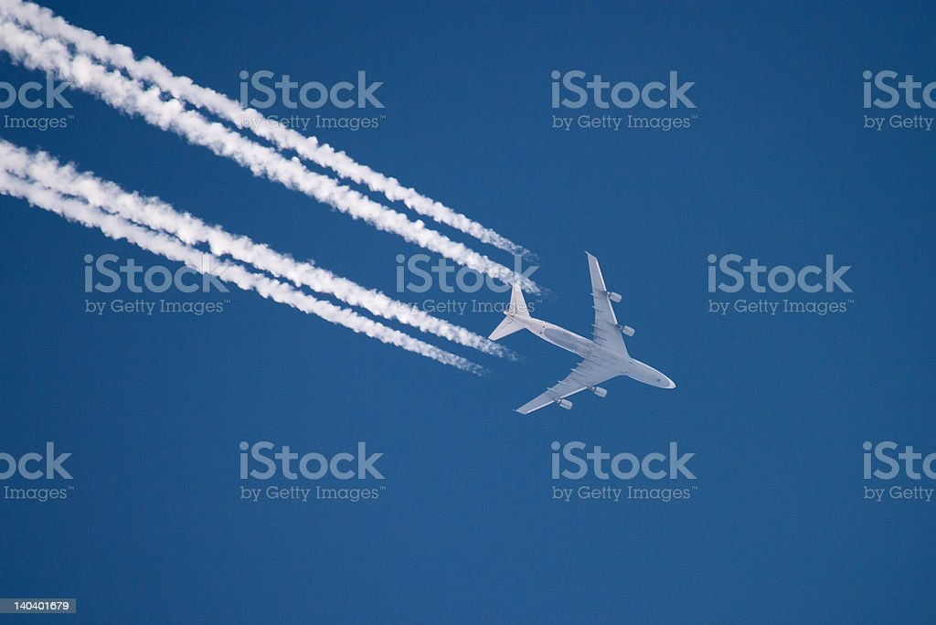 Airplane flying in high altitude leaving contrail stock photo