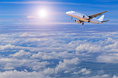 airplane flying in sky above the white clouds