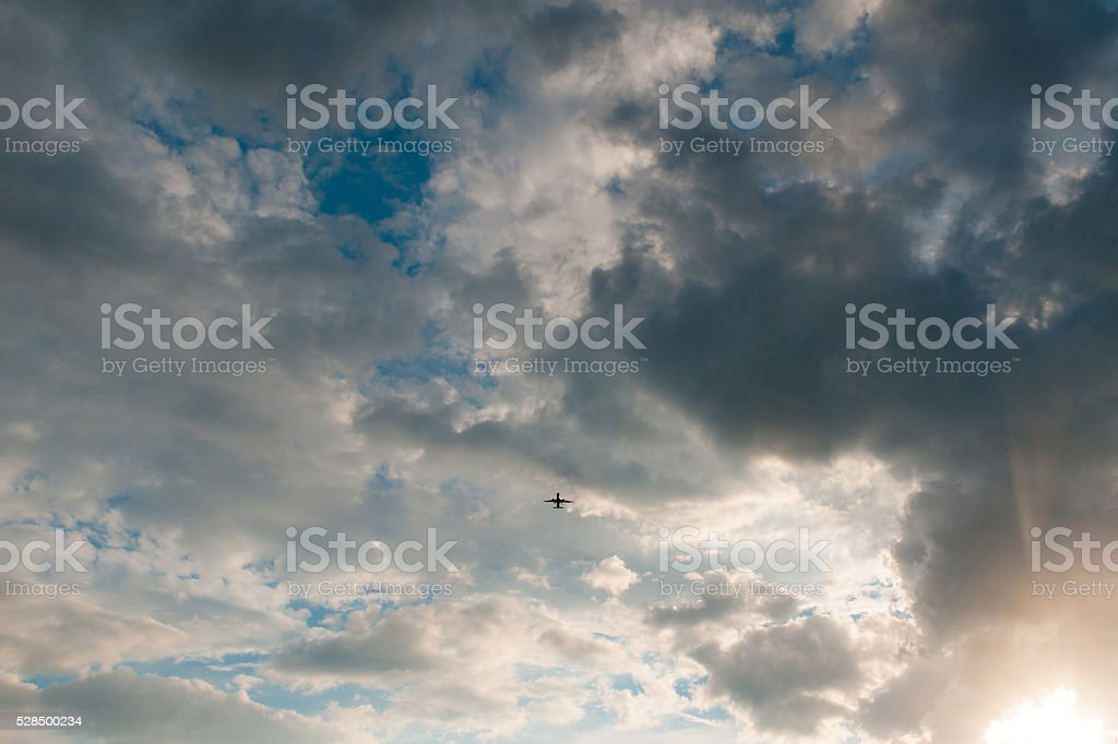 airplane flying in the blue sky with clouds stock photo
