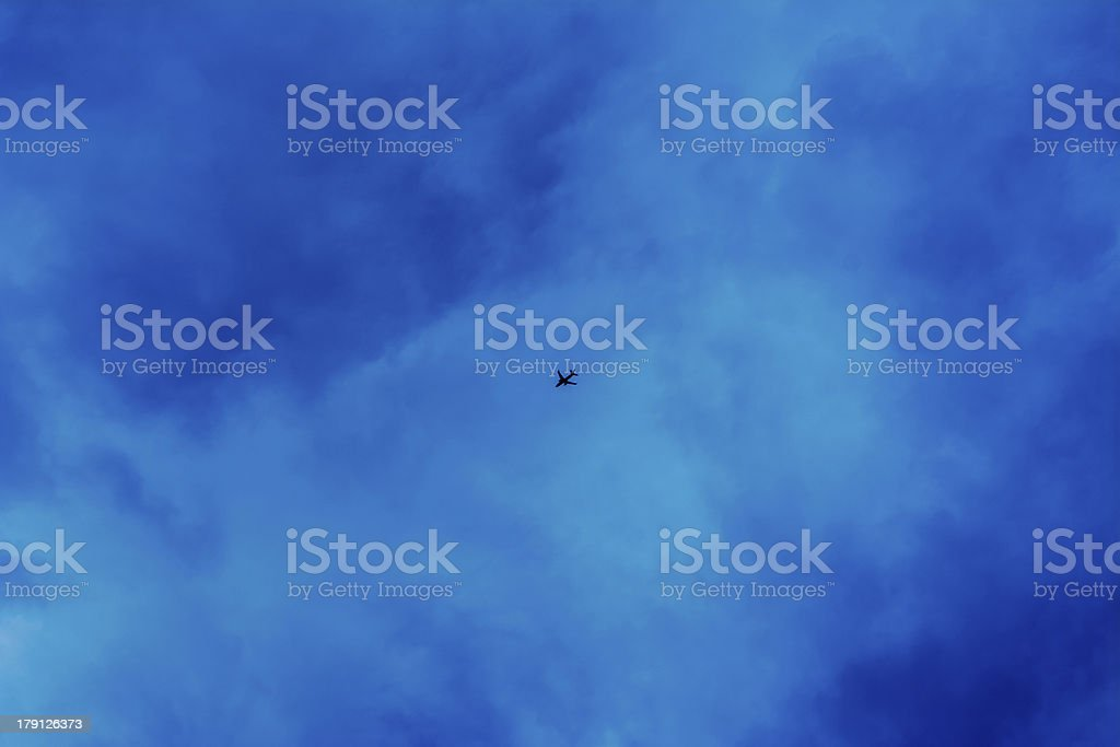 Airplane flying in the dark clouds royalty-free stock photo