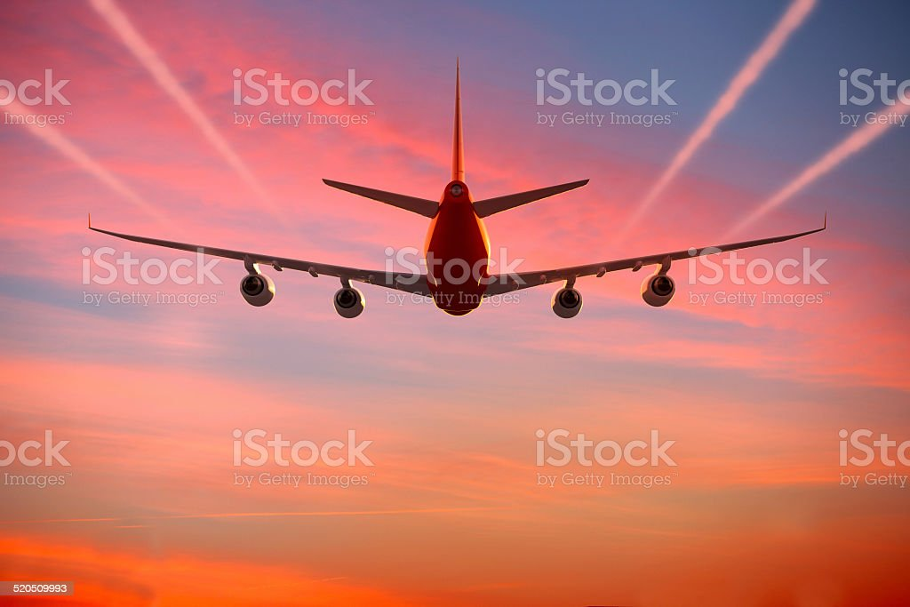 Airplane flying in the sky at sunset with vapor trails stock photo