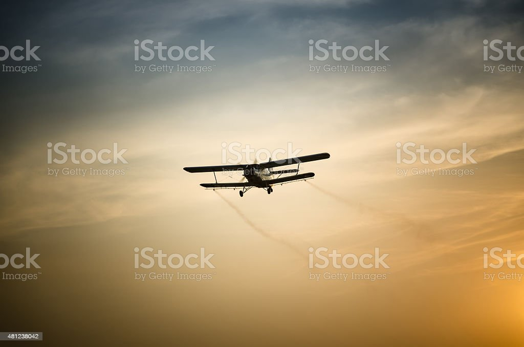 Airplane flying in the sky spraying mosquitoes stock photo