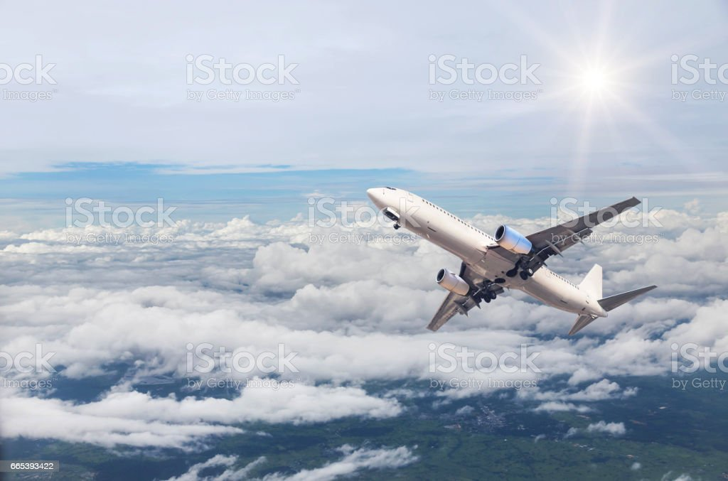 airplane flying in to sky above the white clouds stock photo