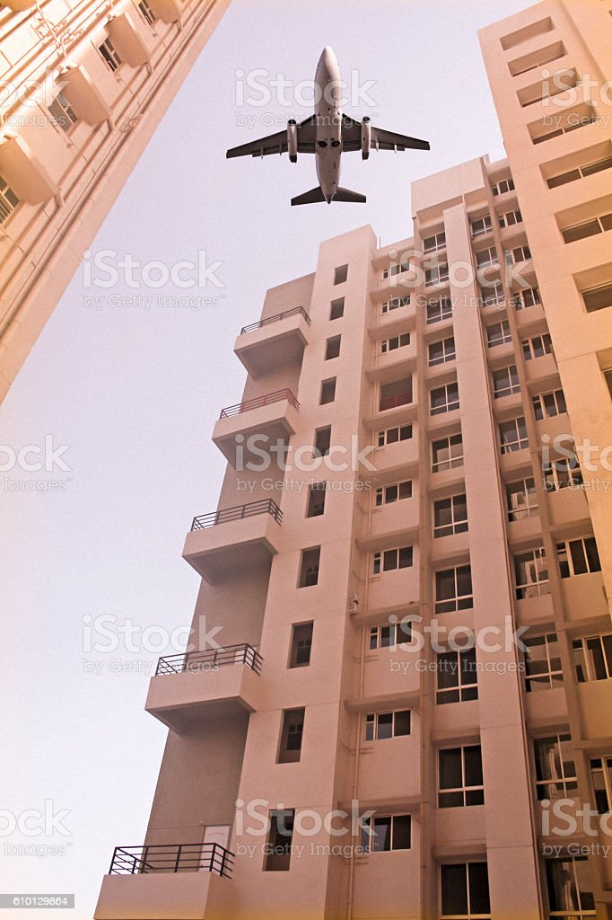 Airplane flying over a Building stock photo