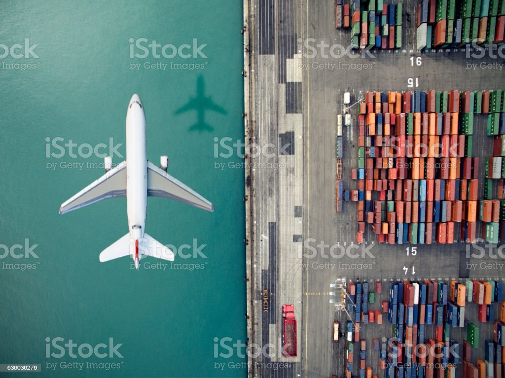 Airplane flying over container port stock photo