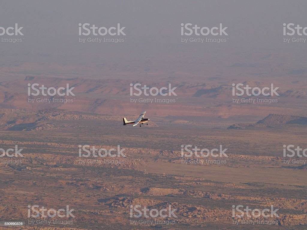 Airplane flying over desert stock photo