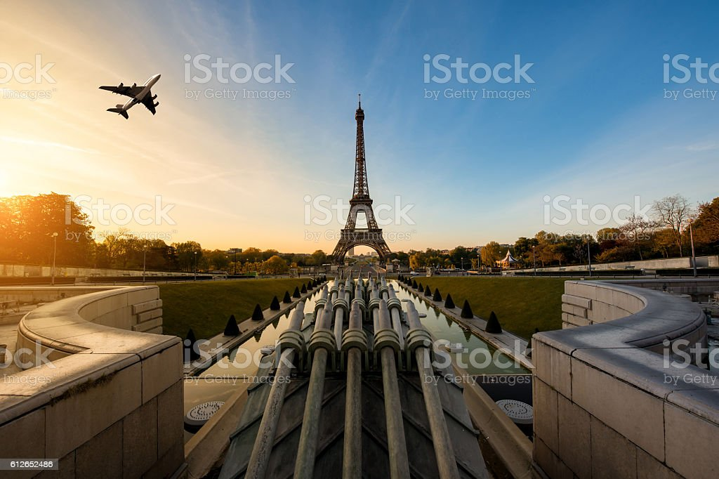 Airplane flying over Eiffel Tower in morning, Paris, France. stock photo