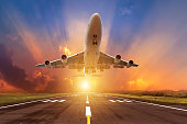 airplane flying take off from runway with sunset