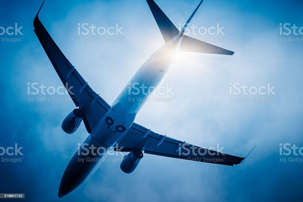 airplane flying through the sky stock photo