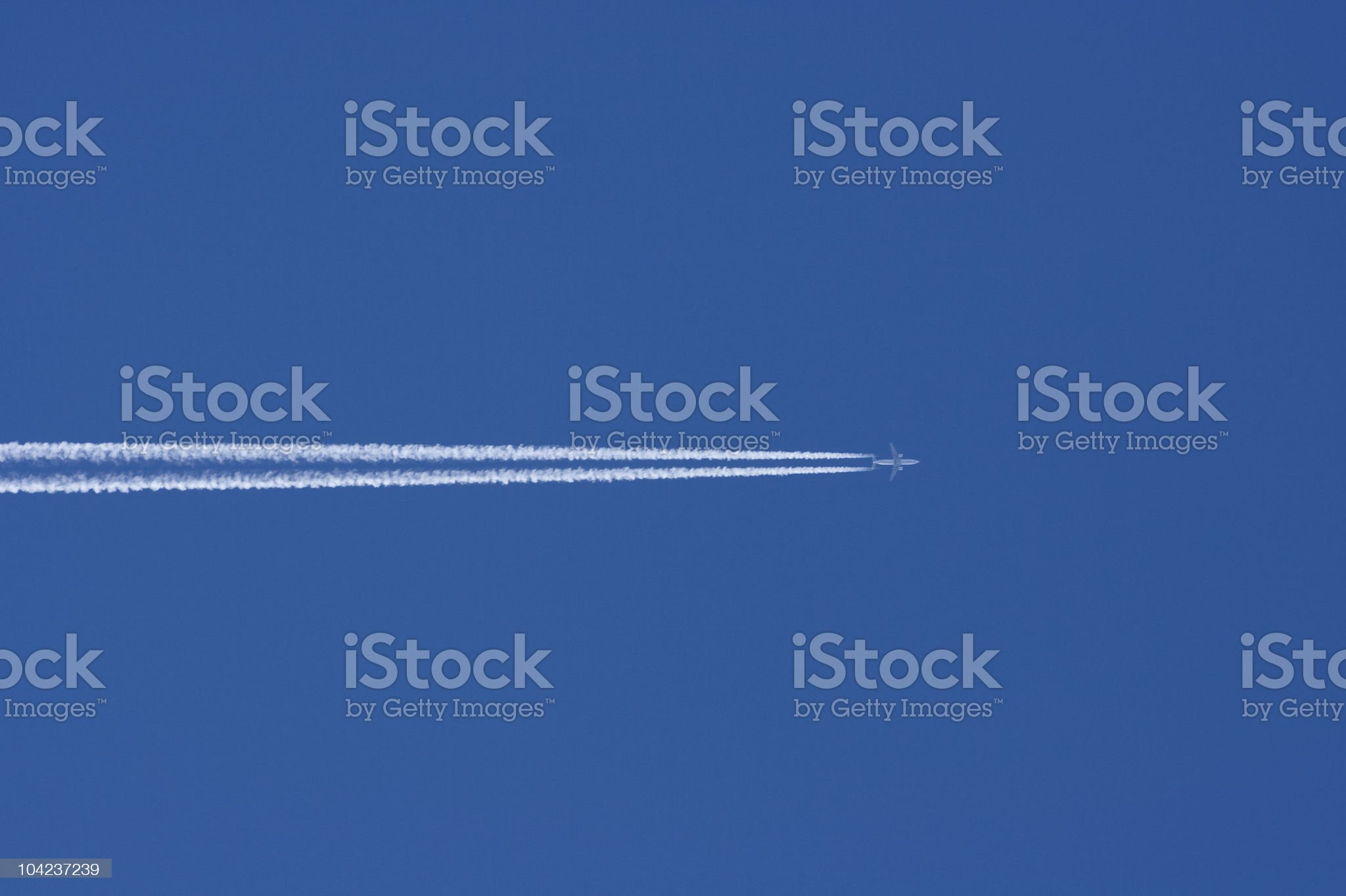 Airplane in a Blue Sky with Vapor Trail royalty-free stock photo