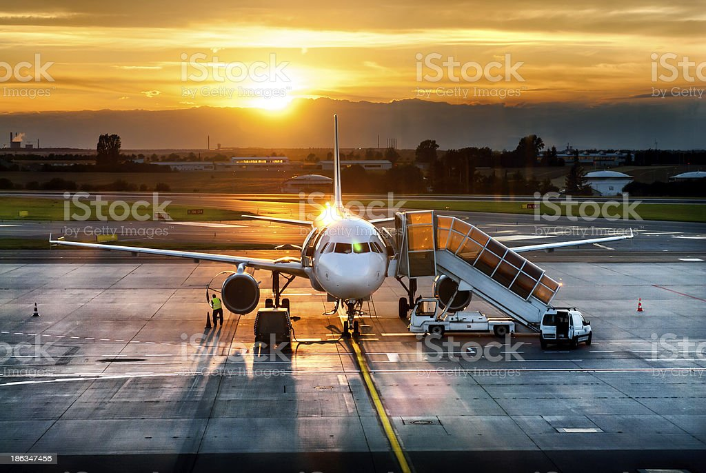 Airplane in an airport at the sunset royalty-free stock photo