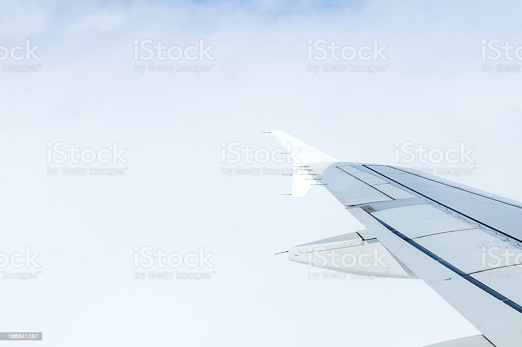Airplane in clouds above earth royalty-free stock photo