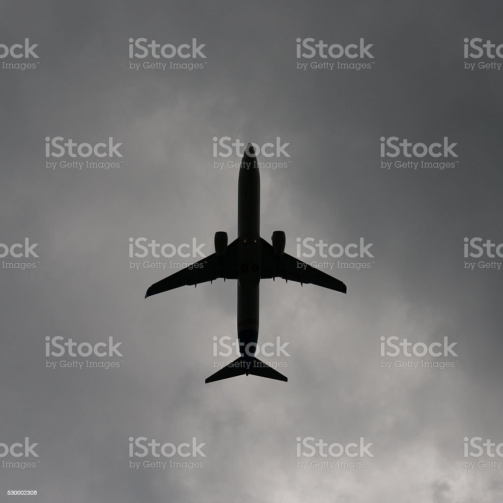 Airplane in cloudy sky stock photo