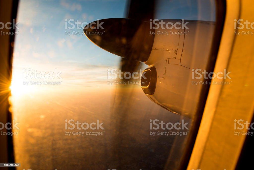 Airplane in flight at sunrise stock photo