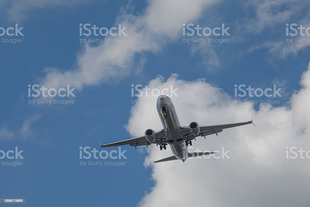 Airplane in flight in a bright summer day stock photo