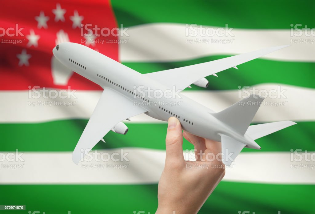 Airplane in hand with flag on background - Abkhazia stock photo