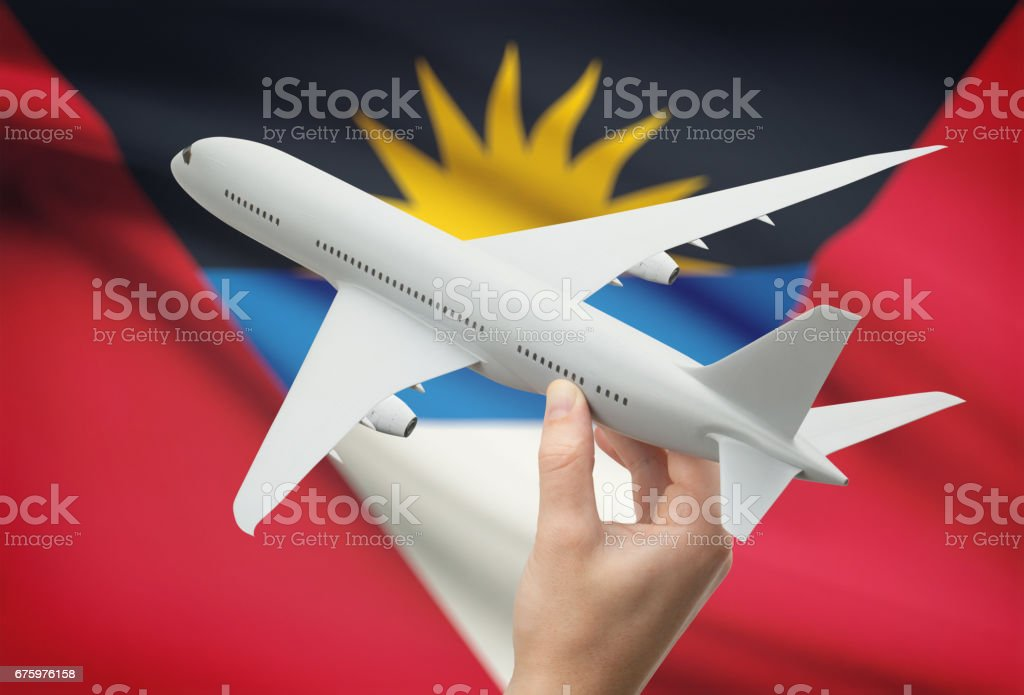 Airplane in hand with flag on background - Antigua and Barbuda stock photo