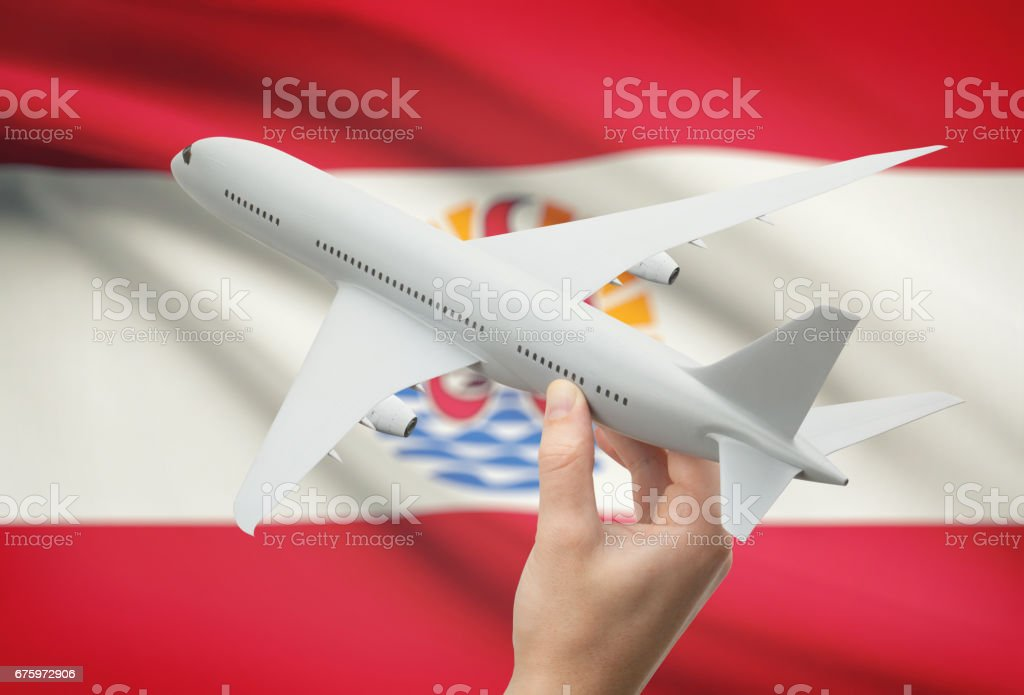 Airplane in hand with flag on background - French Polynesia stock photo