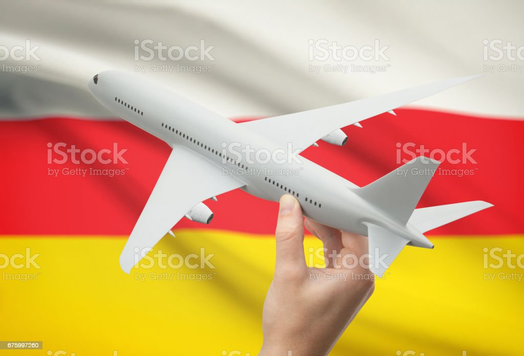Airplane in hand with flag on background - South Ossetia stock photo