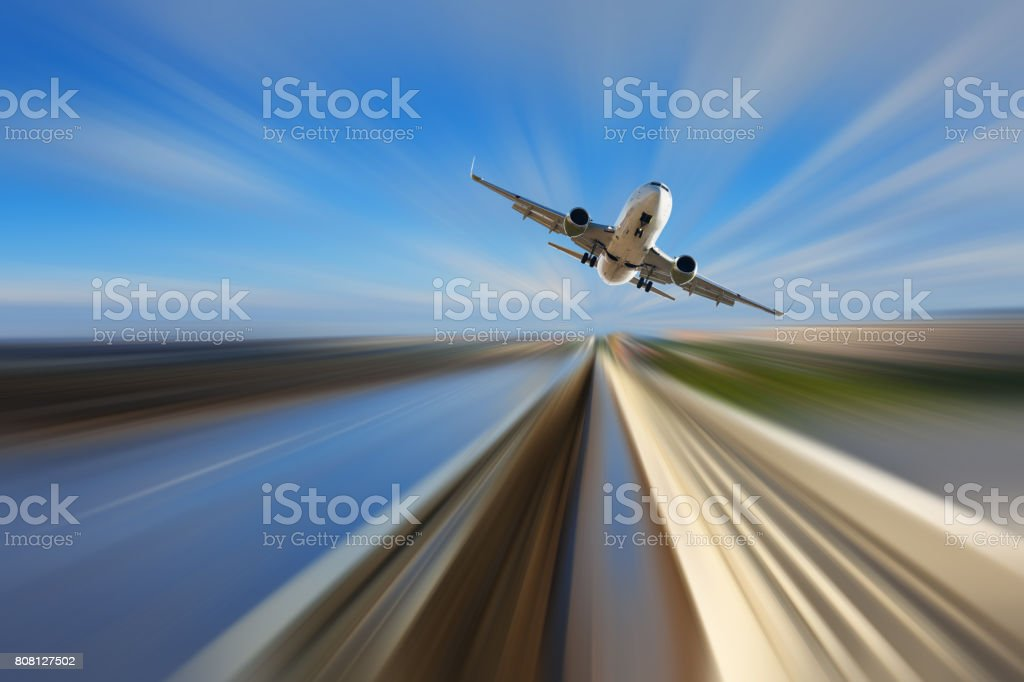 Airplane in motion over roadway stock photo