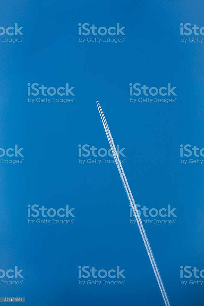 Airplane In Sky With Plane Trails stock photo