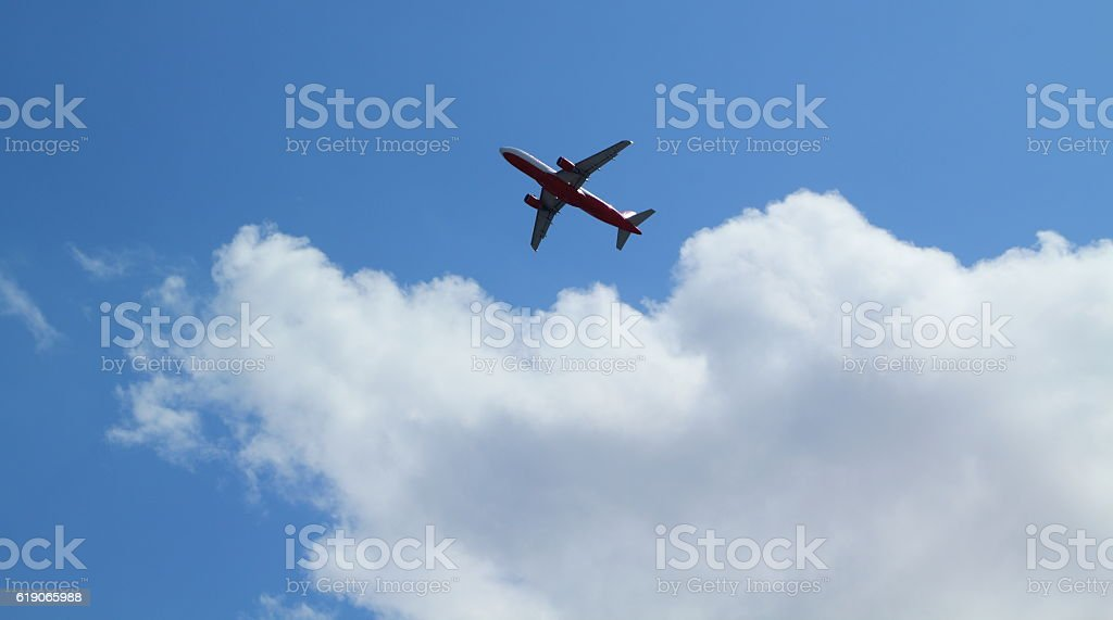 airplane in the cloudy blue sky stock photo
