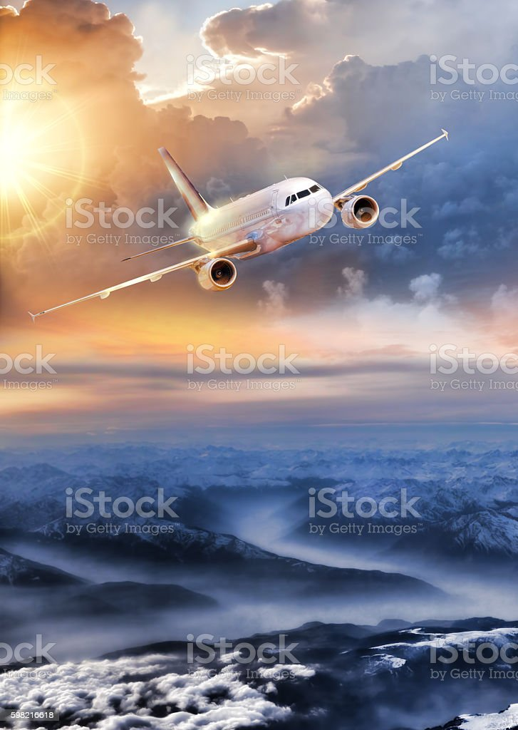 Airplane in the sky over winter Alps stock photo