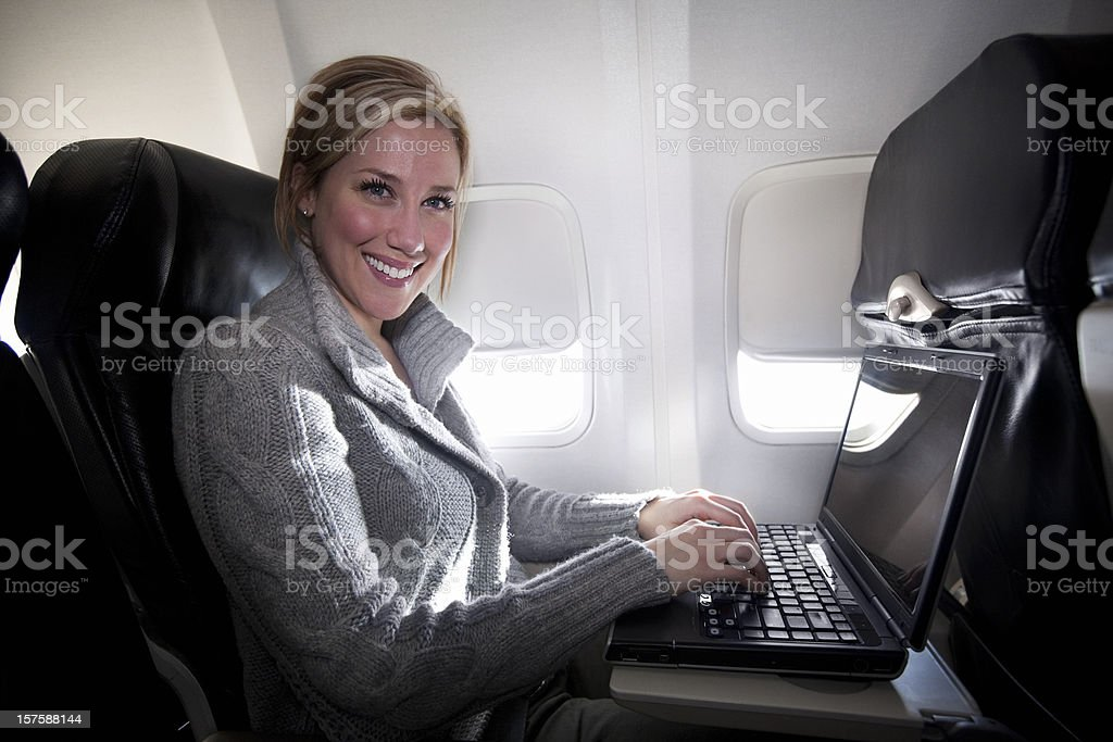 Airplane Interior with Business Woman Using Laptop, Copy Space royalty-free stock photo