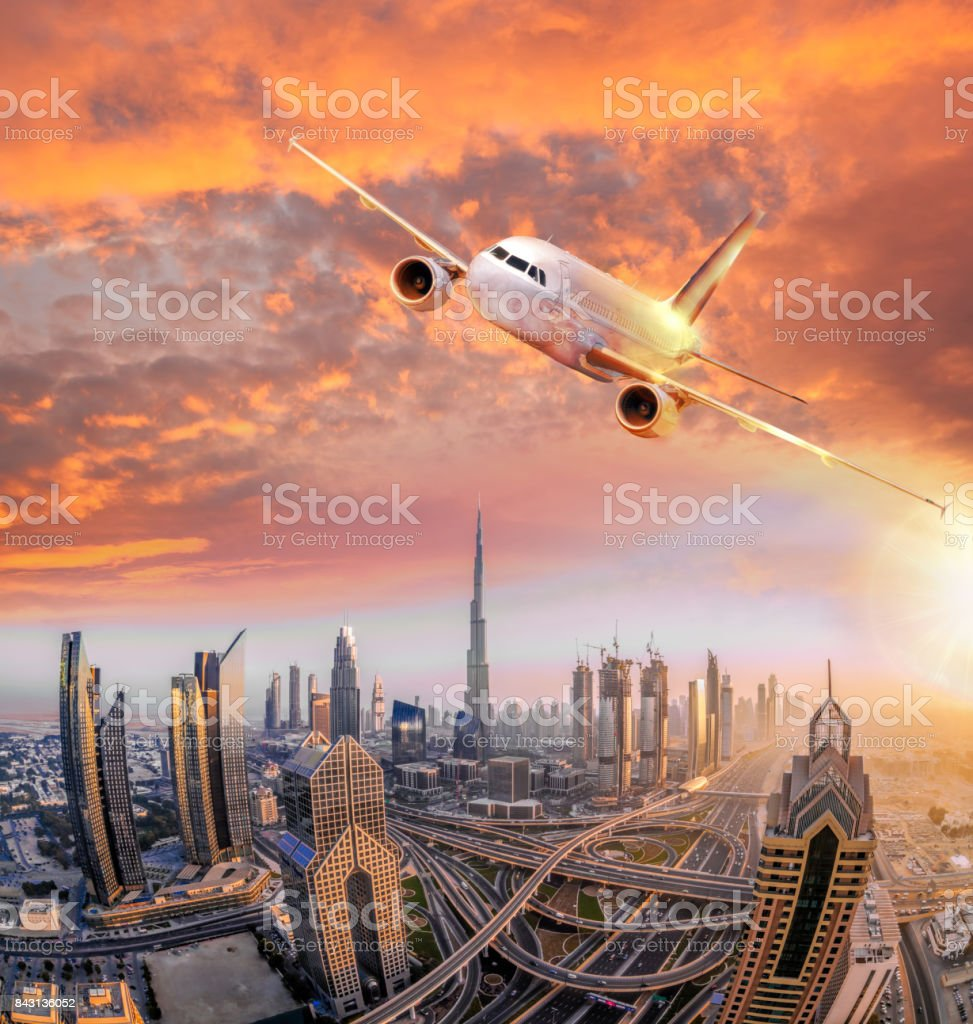 Airplane is flying over Dubai against colorful sunset in United Arab Emirates stock photo