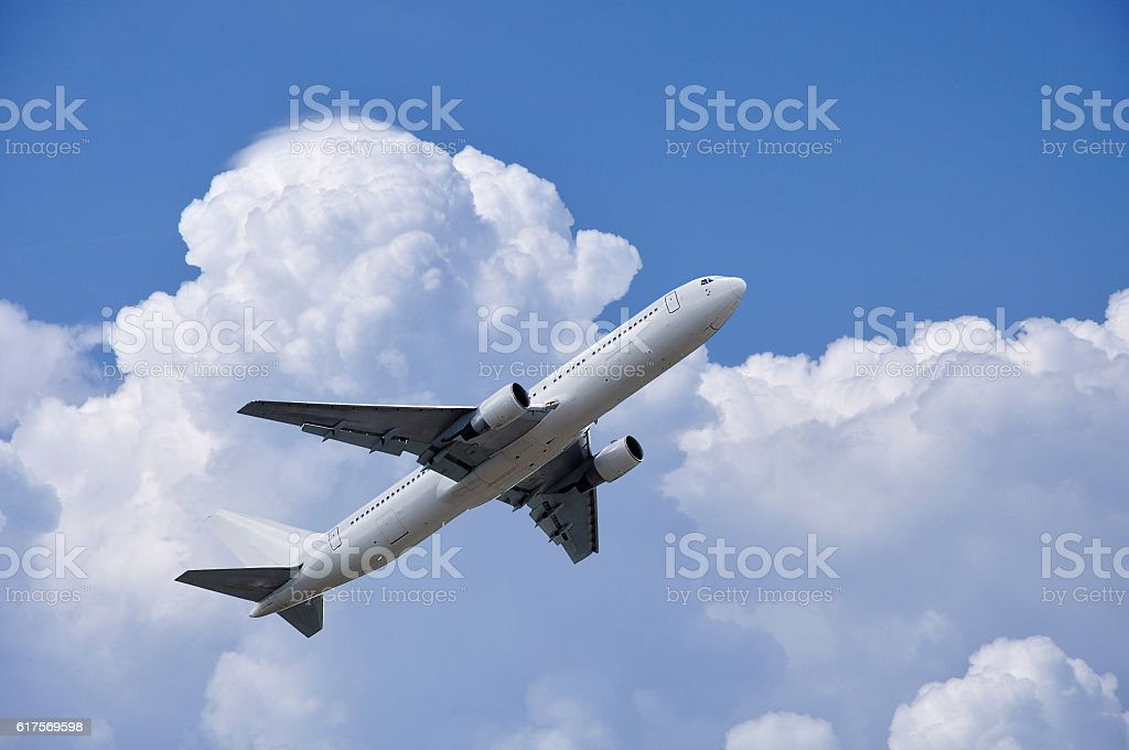 Airplane is takinf off under fluffy clouds in the sky stock photo