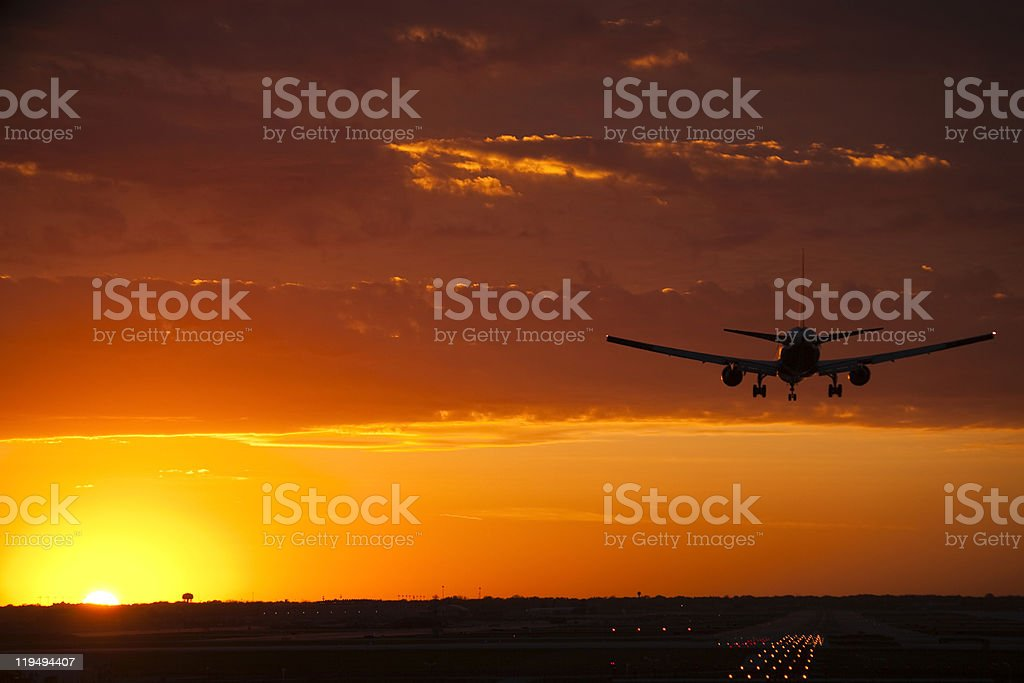 Airplane landing admidst a dramatic sunset stock photo