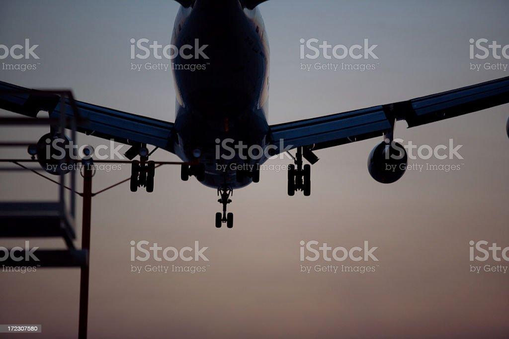 Airplane landing at dusk stock photo
