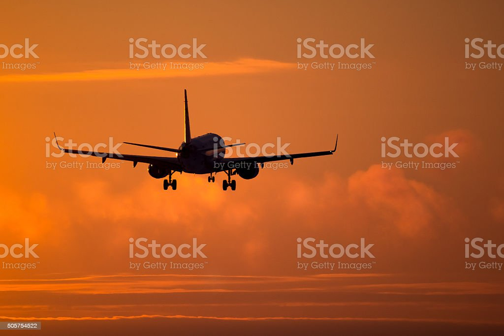 Airplane landing at sunset stock photo