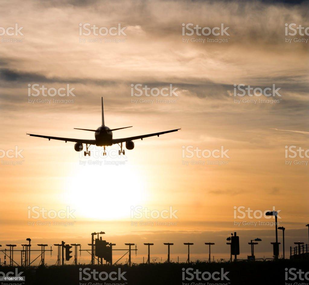 Airplane landing in sunset stock photo