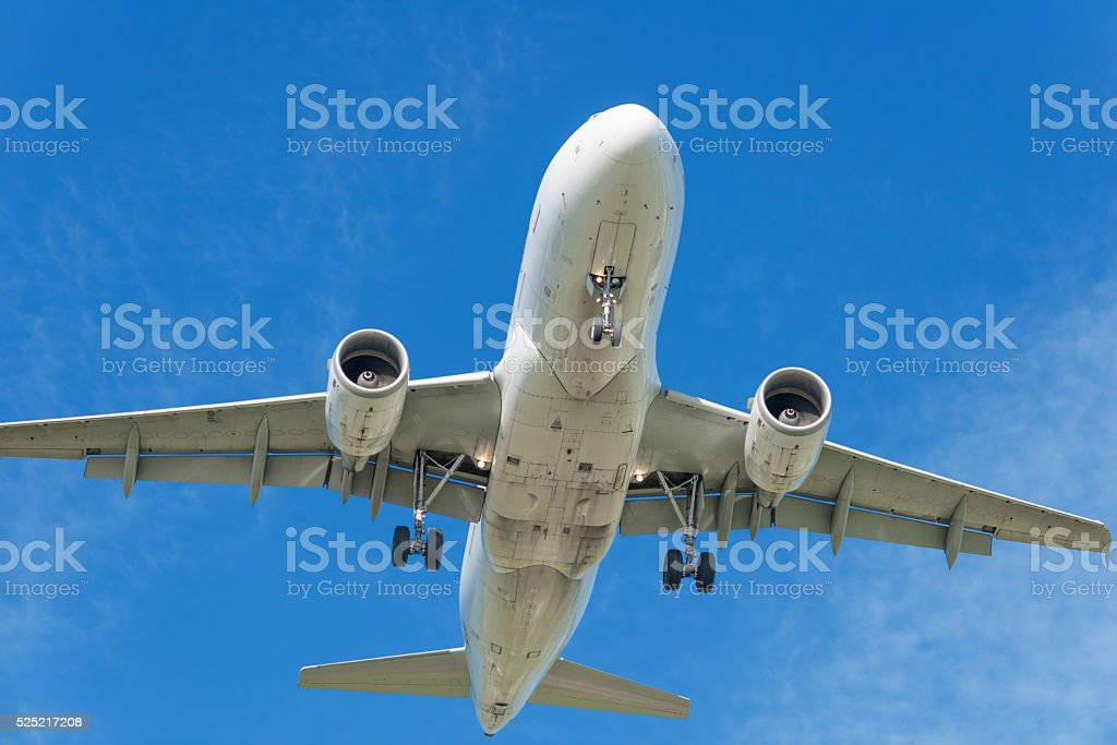airplane landing or starting in front of blue sky stock photo