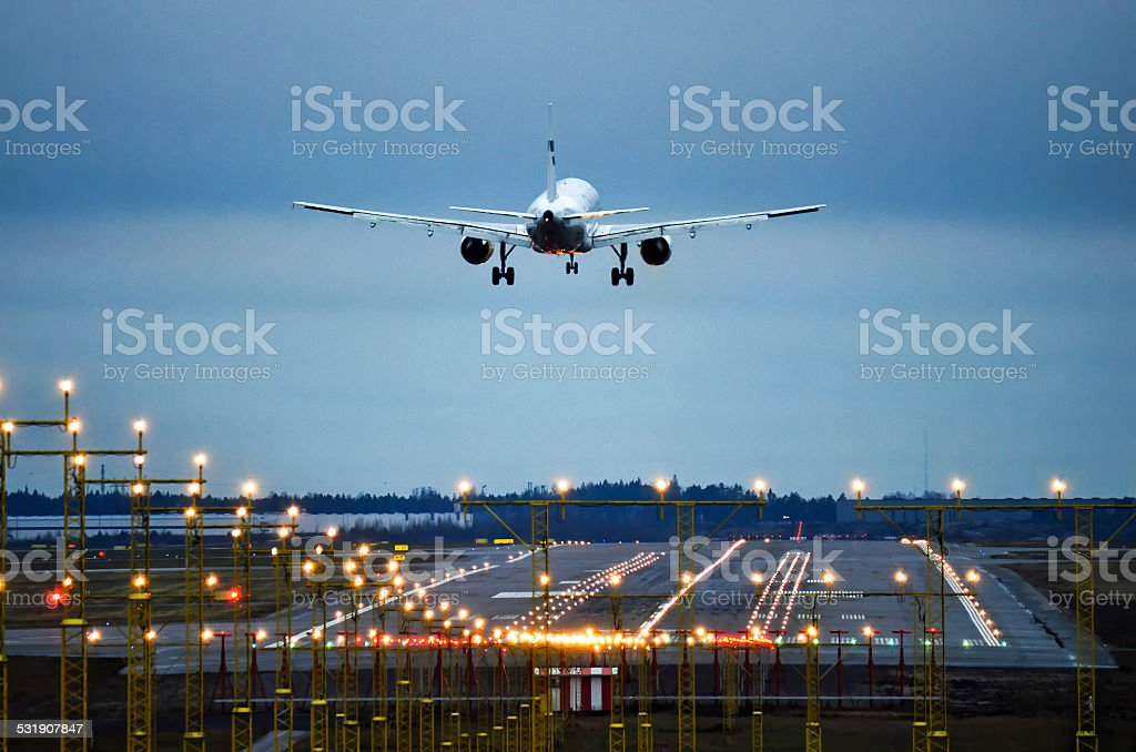 Airplane landing to runway late evening stock photo