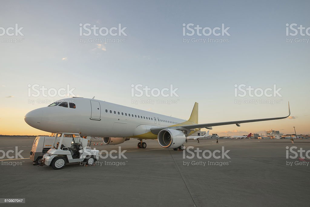 Airplane on airport runway at dusk stock photo