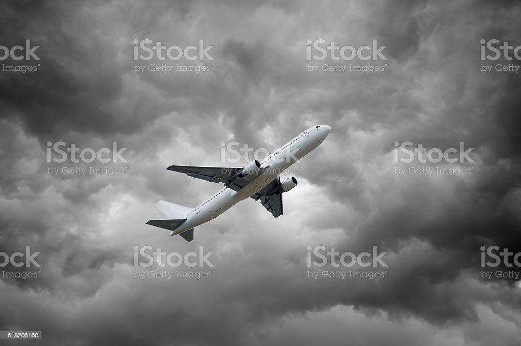airplane is taking off under grey dramatic cloudscape