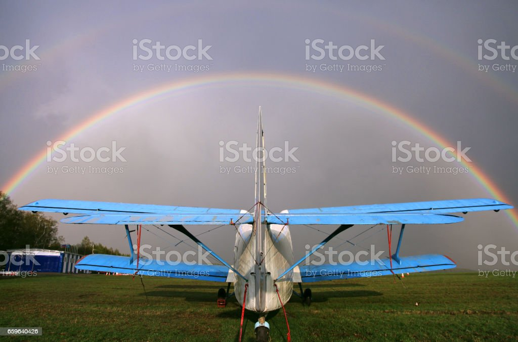 AN-2 airplane on the airfield. Rainbow over the sky. stock photo