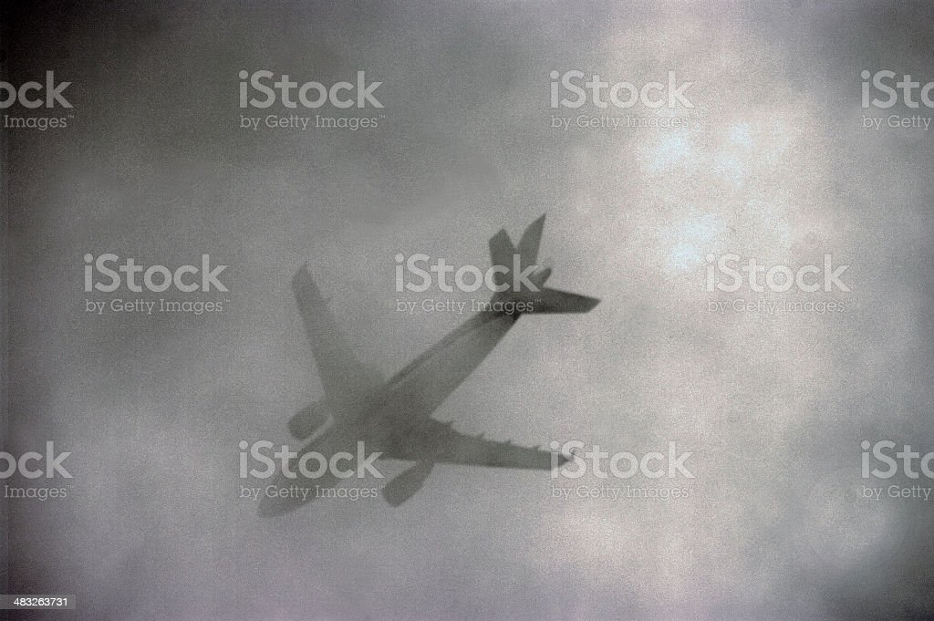 Airplane passing in low clouds stock photo