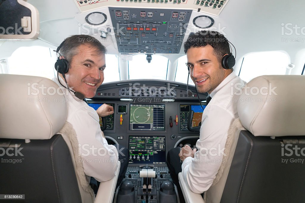 Airplane pilots in the cockpit looking happy stock photo
