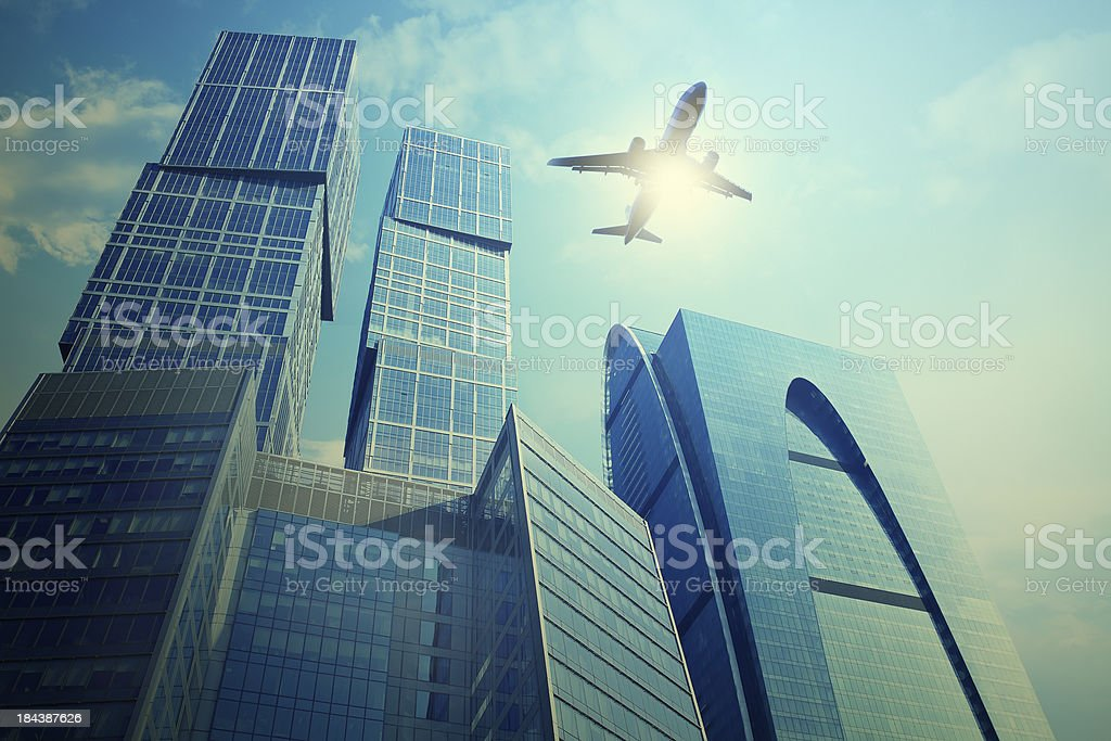 Airplane silhouette over business towers in Moscow stock photo