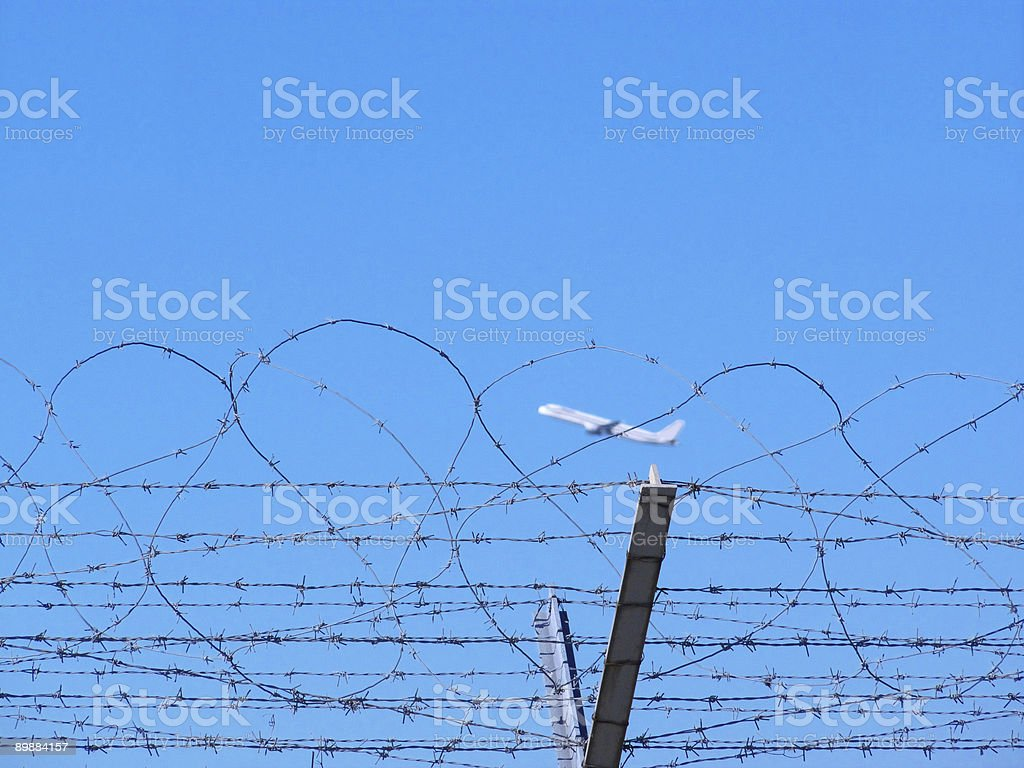 Airplane take off behind barbed wire. stock photo