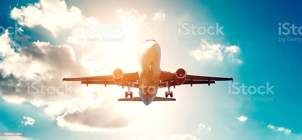Airplane takes off while sun sets in the background stock photo