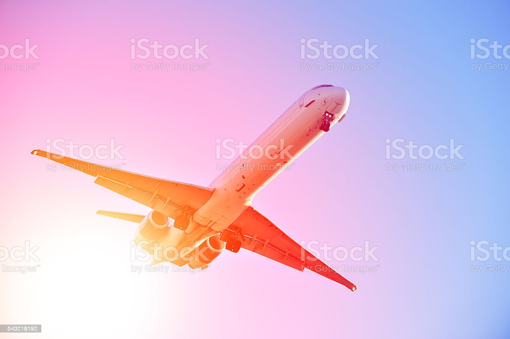 Airplane taking off against dramatic sunset stock photo