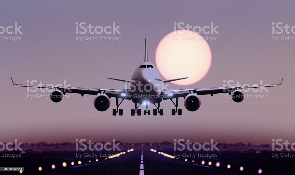 Airplane touch down during sunset stock photo